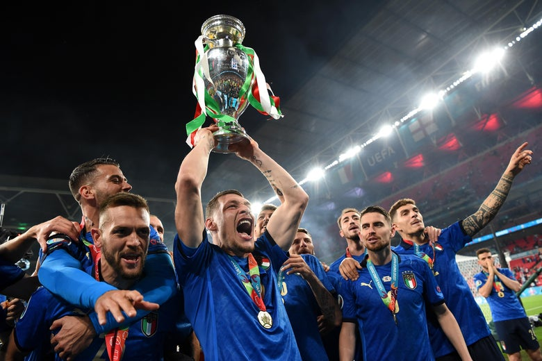 Italian players yell, smile, embrace, and hold up the trophy with stadium lights behind them
