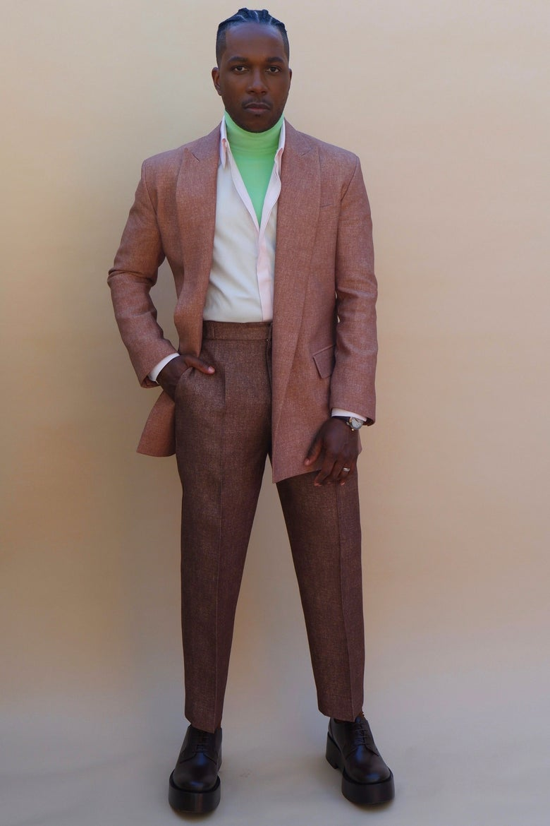 Leslie Odom stands in front of a peach background with one hand in his pants pocket.