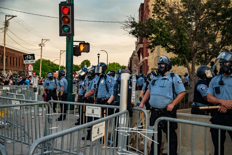 Police in masks stand near barricades and traffic lights.