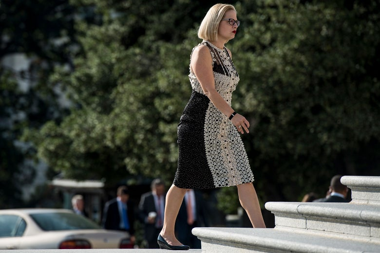 Kyrsten Sinema walks up the House steps in a textured, lacy sleeveless black and cream dress.