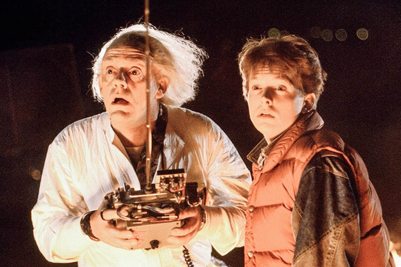 Doc Brown, with his big white hair blown back, holds a giant remote control next to Michael J. Box, in his puffy vest, in Back to the Future