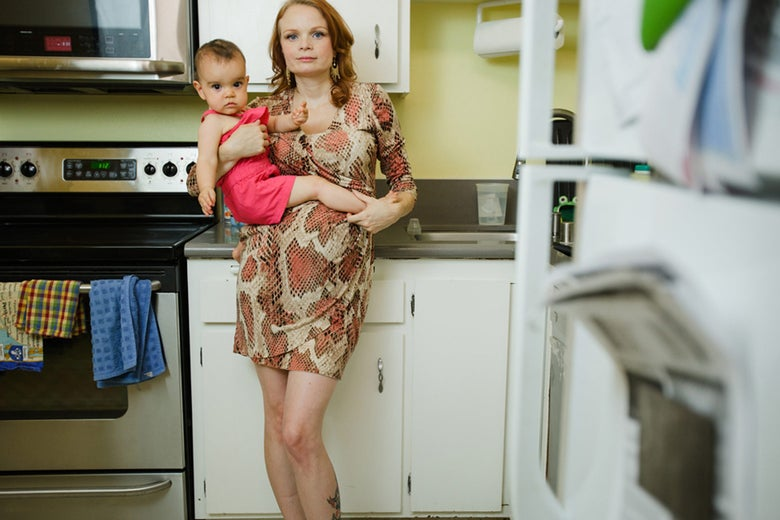 Elizabeth dressed up in her kitchen with a child on her hip.