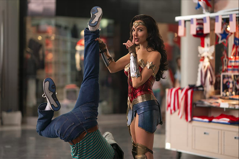 Wonder Woman, standing next to a kiosk in a mall, holds some poor sap upside-down while turning to the camera and holding one finger to her lips