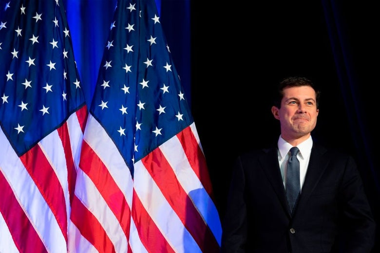 Buttigeg, wearing a suit, walks on to a stage in front of two American flags.