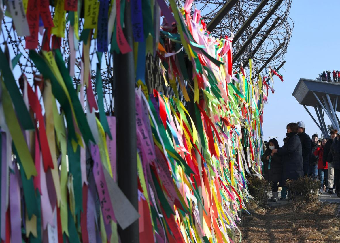 People look at ribbons with inscriptions calling for peace and reunification displayed on a military fence at the Imjingak peace park