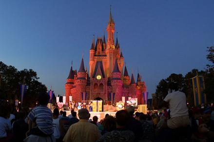 People watch a show on stage in front of Cinderella's castle at Walt Disney World's Magic Kingdom November 11, 2001 in Orlando, Florida.