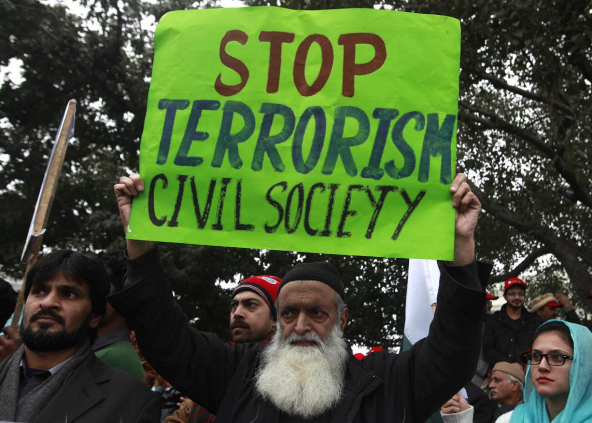 A man holds an anti-Taliban sign along with others during a peace rally in Lahore on January 5, 2015.