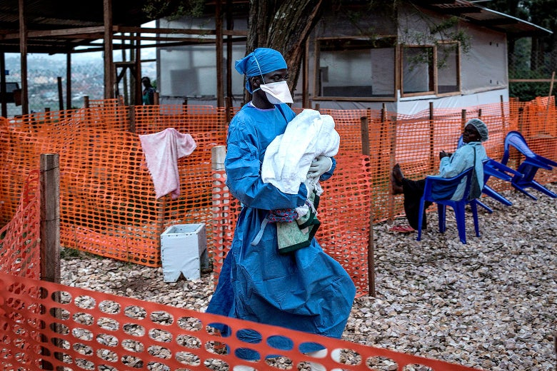 A health worker carries a baby behind orange fencing.