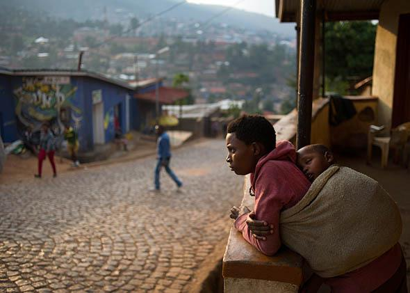 A woman stands on her porch at a suburb set on a hill overlooking Kigali, Rwanda, on March 13, 2014.