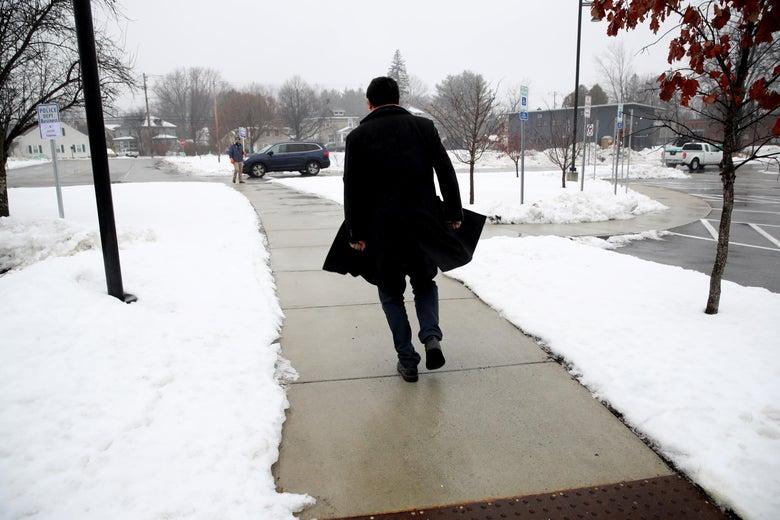 Andrew Yang walks alone on a snowy sidewalk