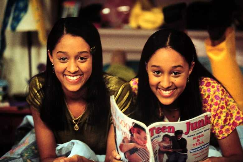 "Tia and Tamera Mowry smiling and leaning forward on their elbows. Tamera holds a magazine with ""Teen Junk"" on the cover."
