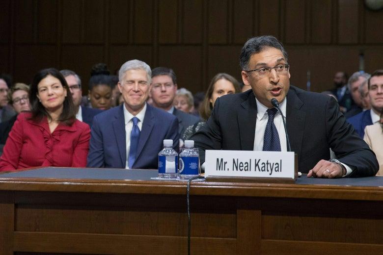 Katyal testifies before the Senate as Gorsuch smiles, sitting in the gallery behind him.