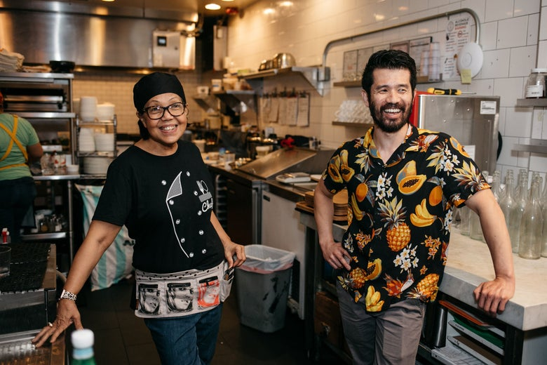 Two people smiling in a restaurant kitchen.