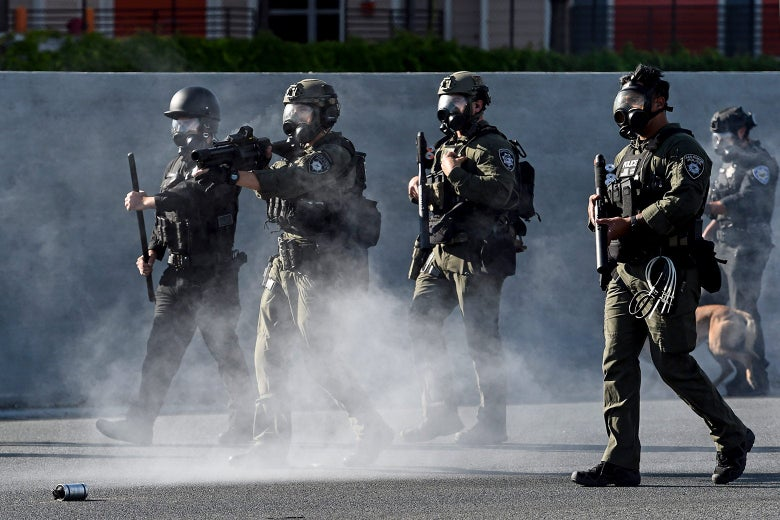 Police in tactical gear carry guns and throw tear-gas canisters.