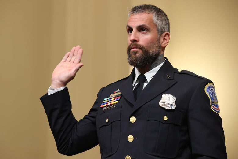 In his officer uniform, Fanone raises his right hand to swear to tell the truth.