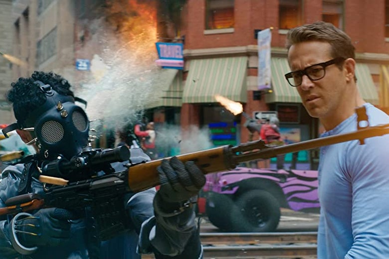 Ryan Reynolds, wearing a blue shirt, looks with confusion at a man in a gas mask firing a rifle.