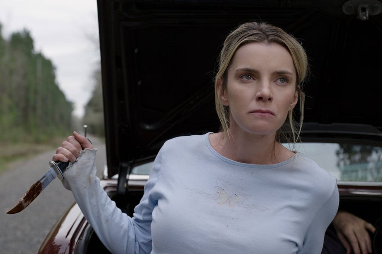 Betty Gilpin holds up a bloody Rambo knife
