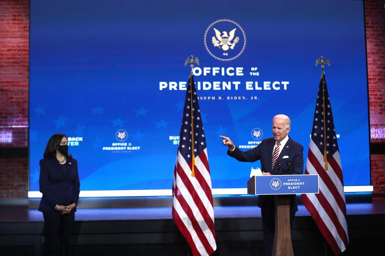 "Joe Biden is standing at a podium, pointing his finger into the open as Kamala Harris stands to his right, looking on. An ""OFFICE OF THE PRESIDENT ELECT"" sign is in the background."
