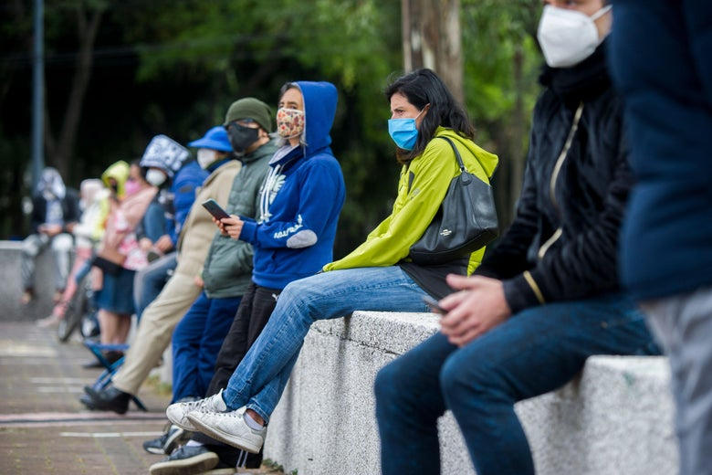 People wearing masks sit on a low wall.