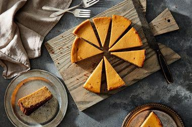 Slices of orange cheesecake on a cutting board with two slices nearby on plates.