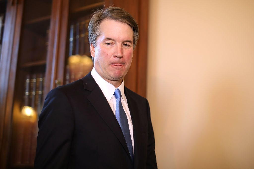 Kavanaugh looks down and to his right against the backdrop of a Capitol Hill office.