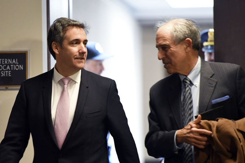 A smiling Cohen converses with Davis as they walk down a hallway.