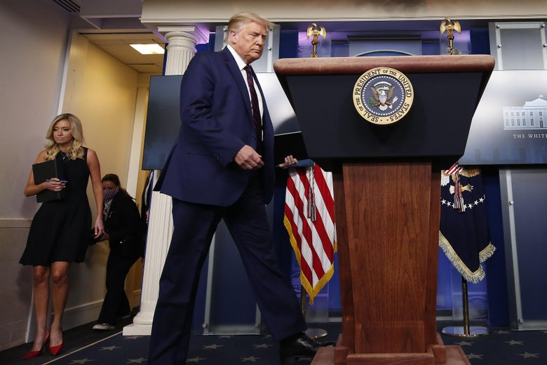 Donald Trump, seen full length, strides from left to right toward the lectern with the presidential seal in the White House briefing room.