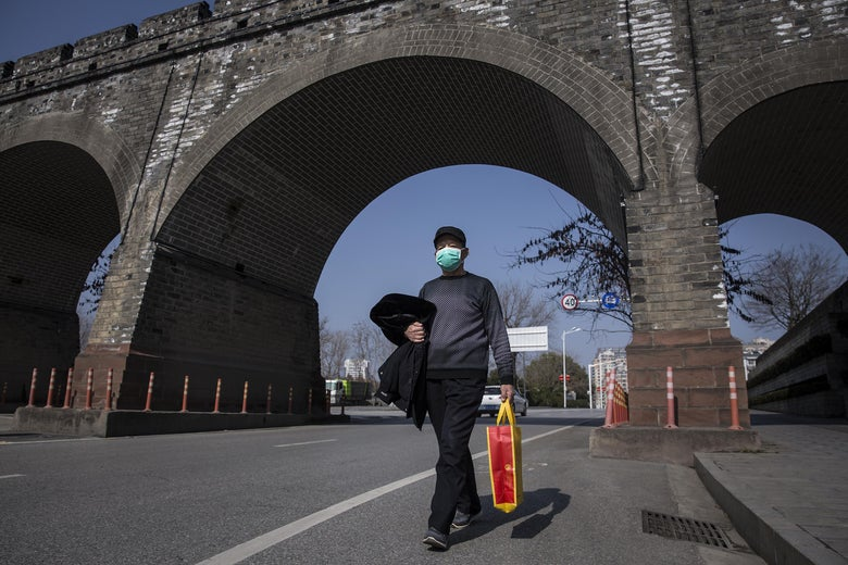 A man wearing a protective mask walks under a bridge.