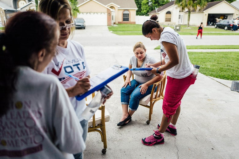 A group from Mi Familia Vota registering people to vote in a driveway.