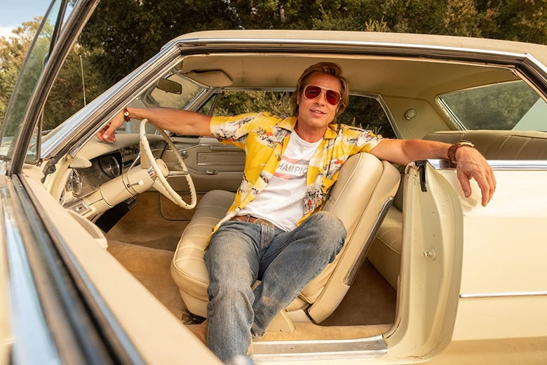 Brad Pitt, in costume as Cliff Booth in a still from Once Upon a Time in Hollywood, lounging in a cream colored Cadillac.