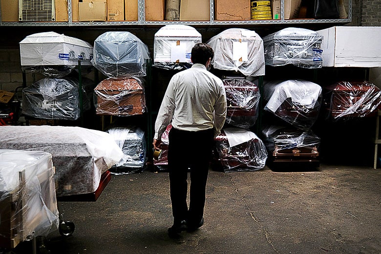 A man in a white shirt and dark pants stands with his back to the camera in front of a rack of coffins in various colors, individually wrapped in clear plastic sheeting, stacked three rows high.