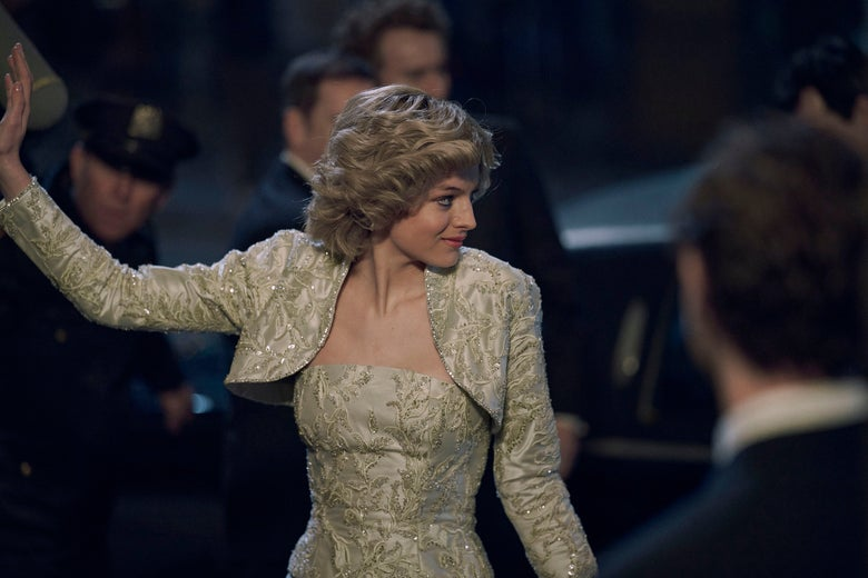 Emma Corrin as Diana in a gold brocade dress, waving with her right arm and looking to her left as she makes her entrance at an event, with security in the background