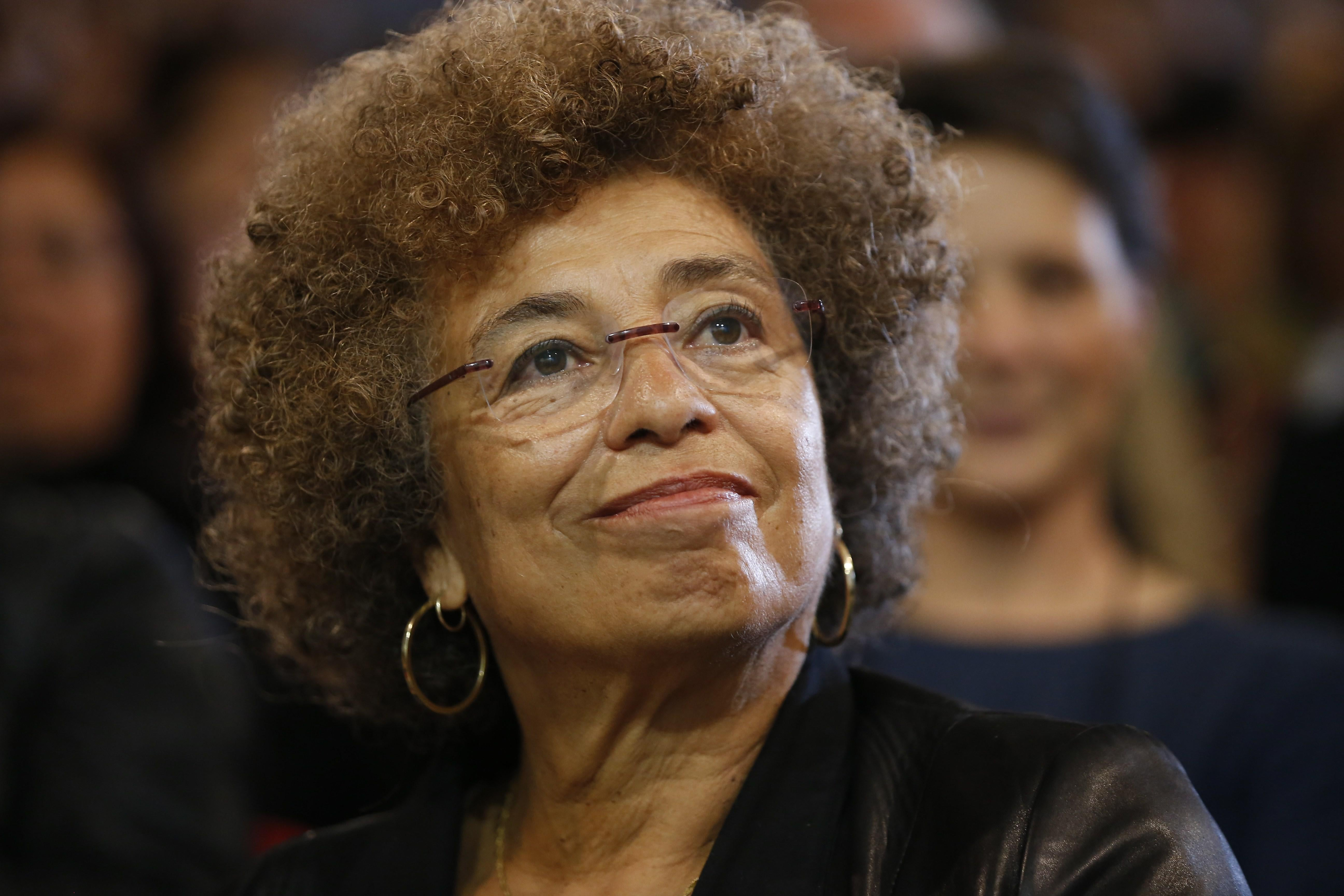 Angela Davis, sitting in front of a crowd, smiles toward the camera