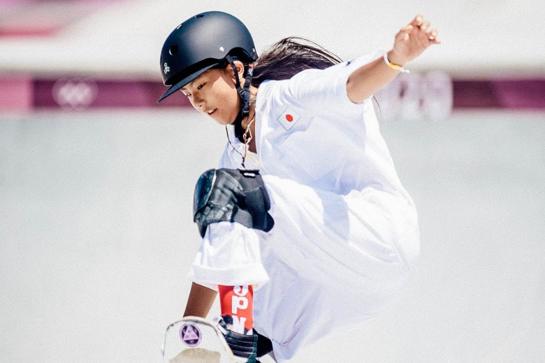 Hiraki on her skateboard ascending the park ramp, looking at her feet, left arm outstretched, in knee pads and helmet