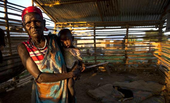 A woman holds her grandson, poor family living in a small shack in the city center July 19, 2012 in Juba, South Sudan.