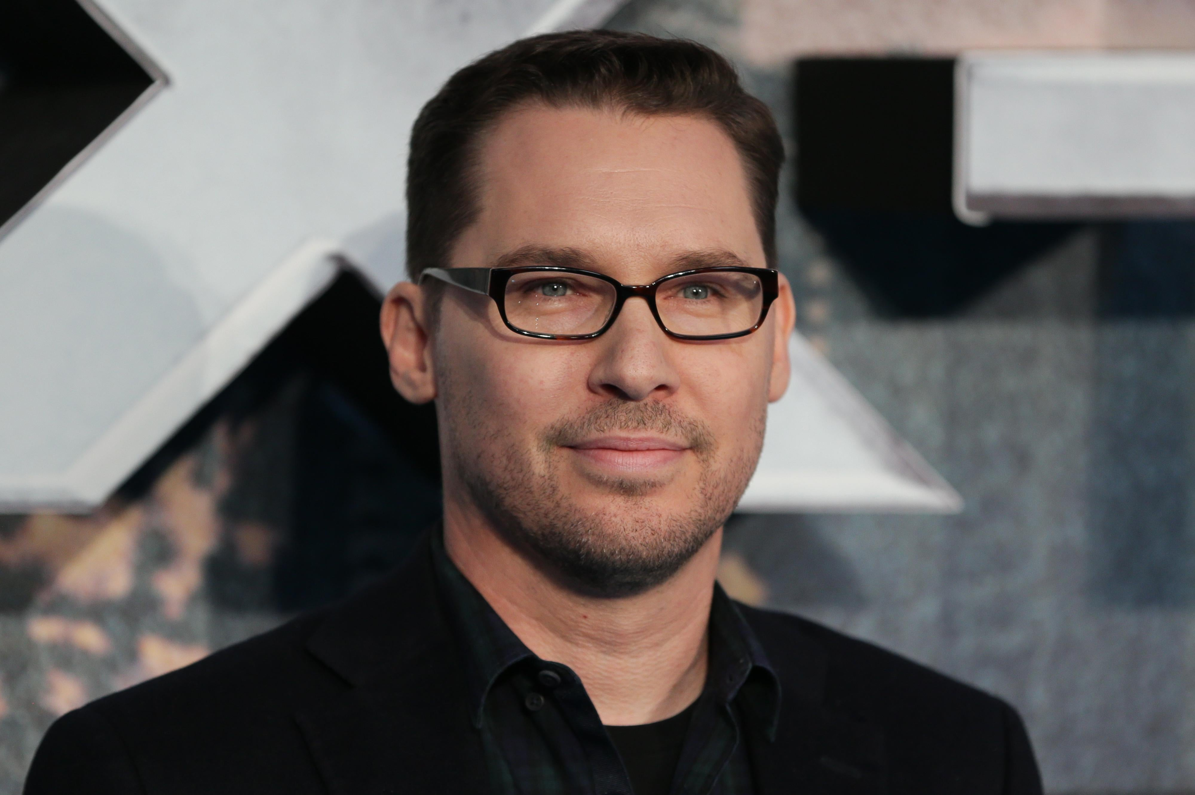 Bryan Singer, wearing a black suit and black glasses, stands in front of a large silver X.