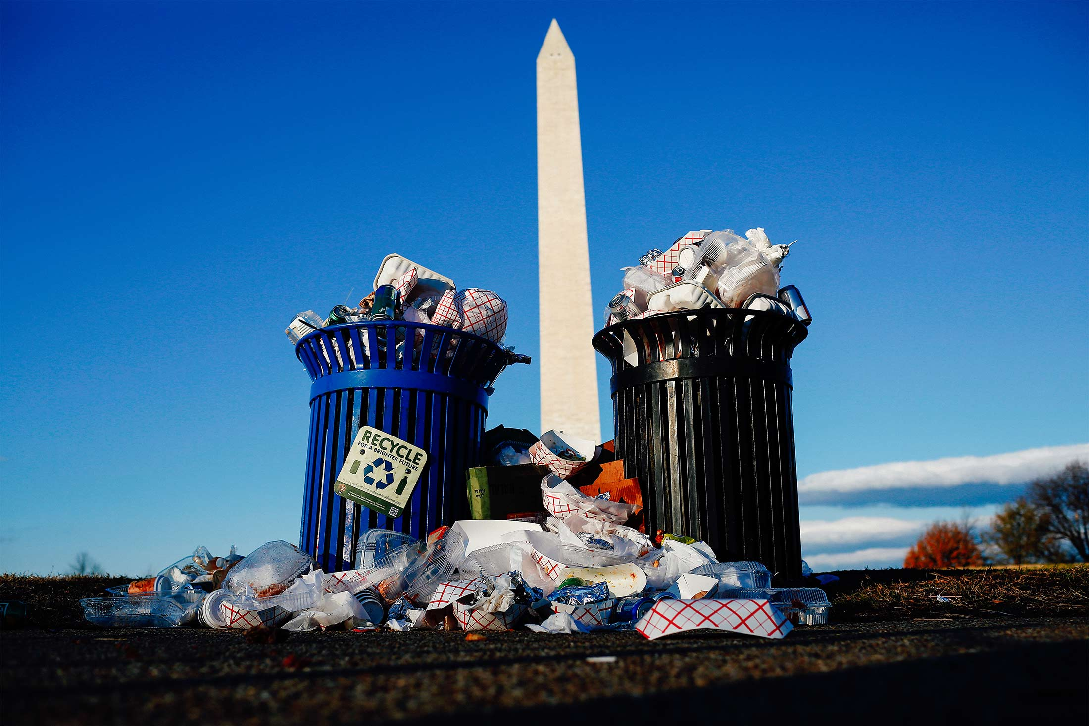 Trash overflows from a trash bin and a recycle bin, in front of the Washington Monument.