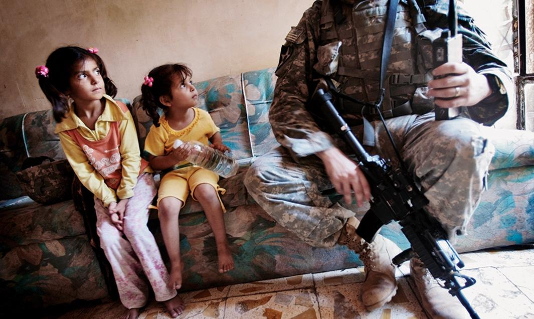 Two Iraqi girls look at Staff Sgt. Nick Gibson while he canvasses the tense Dora neighborhood of Baghdad on June 21, 2007. U.S. soldiers canvased their areas almost every day, attempting to get to know the residents and find insurgents.