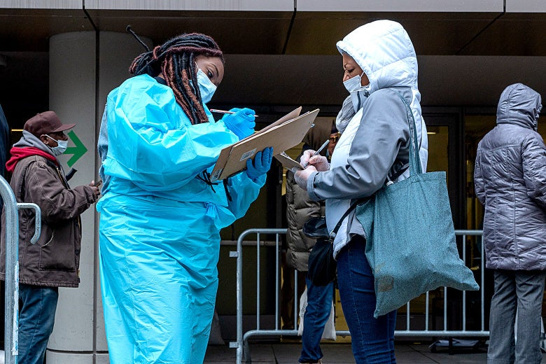 A woman in protect gear writes something on a clipboard next to a woman in a surgical mask.