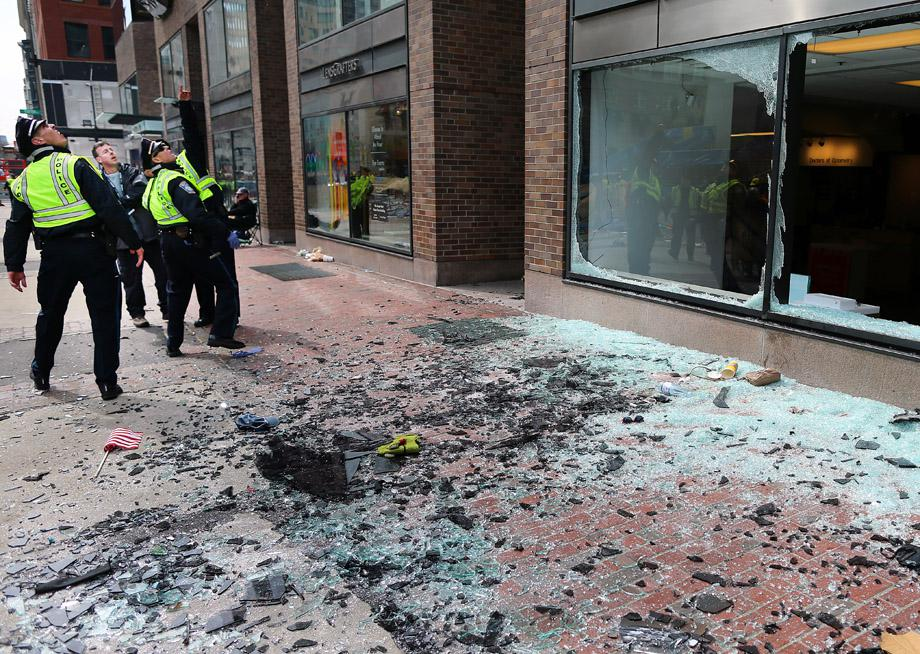 Boston Police look at blown out windows at the scene of the first explosion on Boylston Street near the finish line of the Boston Marathon.