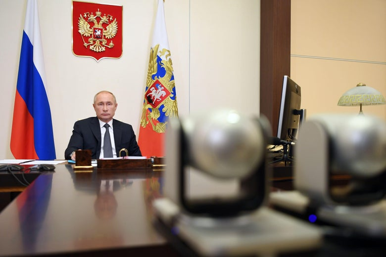 Russian President Vladimir Putin sits behind a desk during a teleconference.