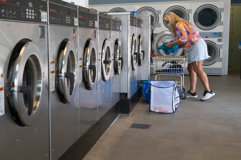 A woman wearing a face mask does her laundry in a laundromat.