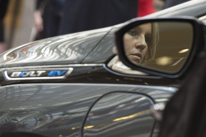 A woman's face appears in a driver's side mirror, against a Chevy Bolt in the background.t.