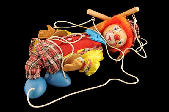 Creepy clown puppet in a tangled pile