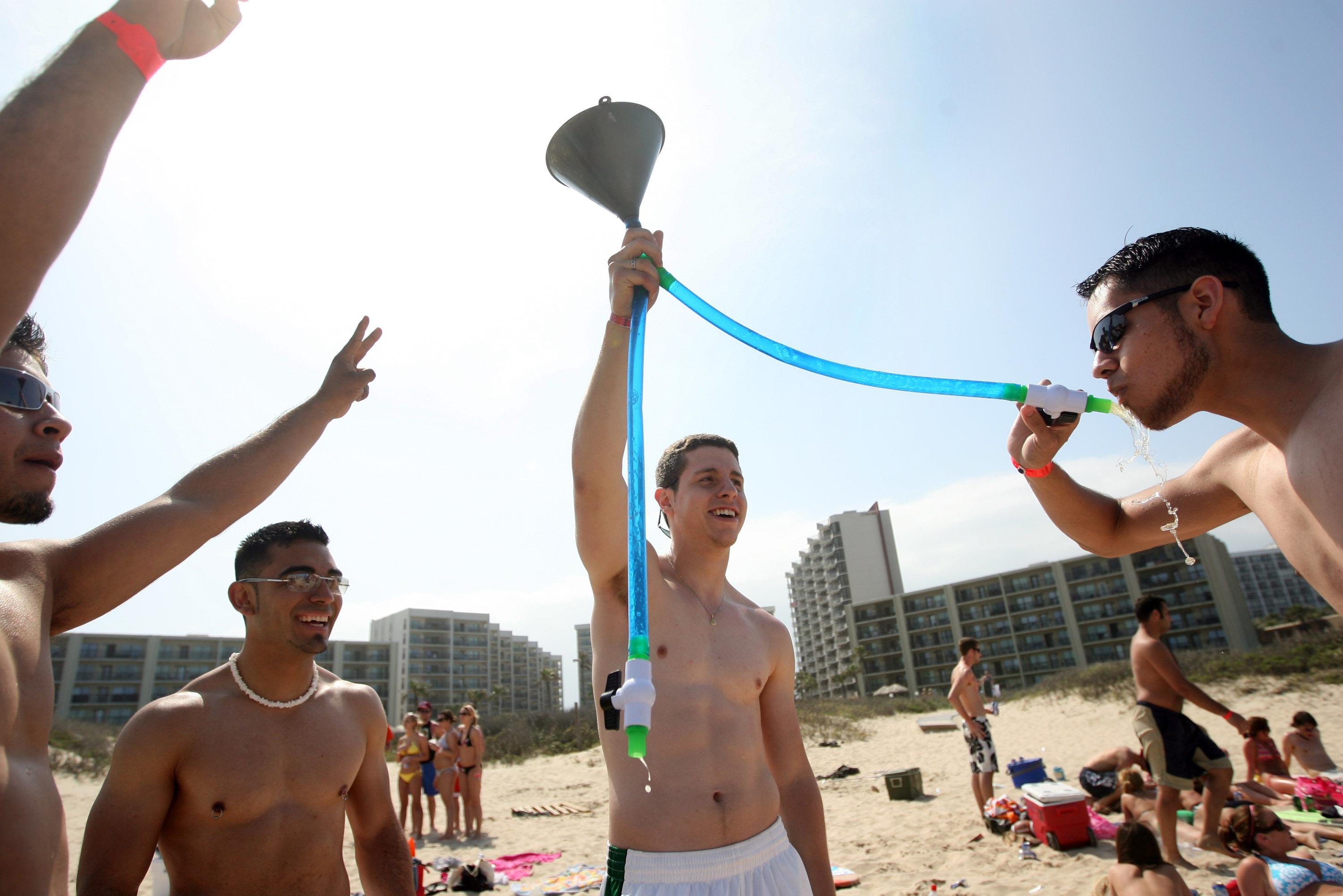 Students from the University of Texas-El Paso drink beer from a funnel on the beach during the annual ritual of Spring Break March 25, 2008, on South Padre Island, Texas.