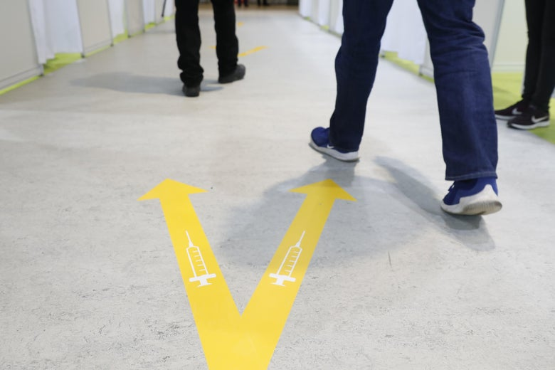 People's feet beside a yellow V painted on the floor, with a syringe in each arm of the V.