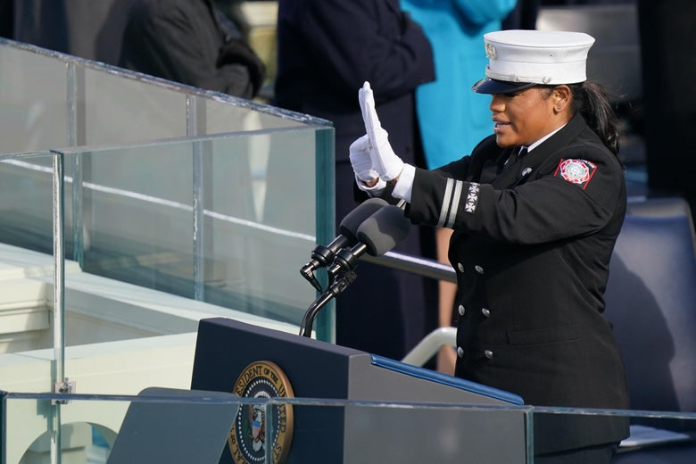 A woman in uniform at a lectern signs.