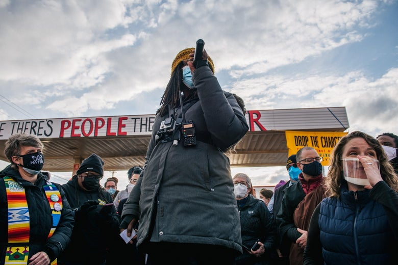 A woman in a puffy winter coat and a yellow beanie with a GoPro on her chest speaks into a microphone with a crowd behind her in George Floyd Square.