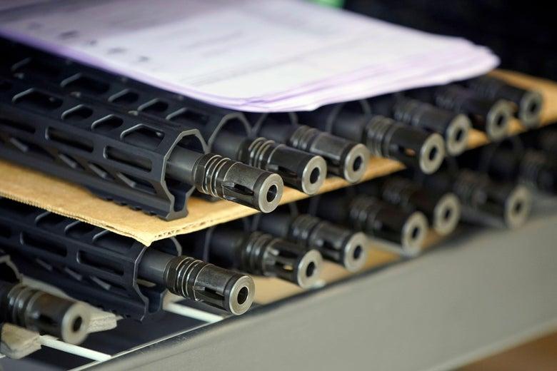 AR-15 style rifle barrels sit on a shelf.