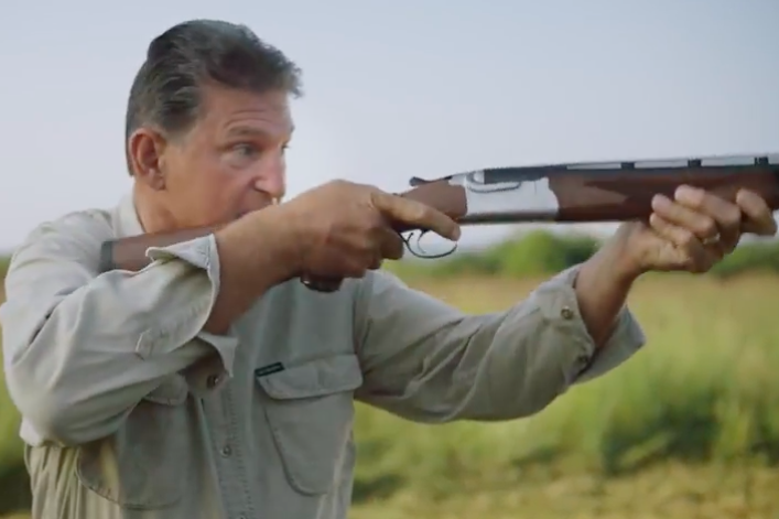 Manchin, standing in a field, levels and aims a shotgun.